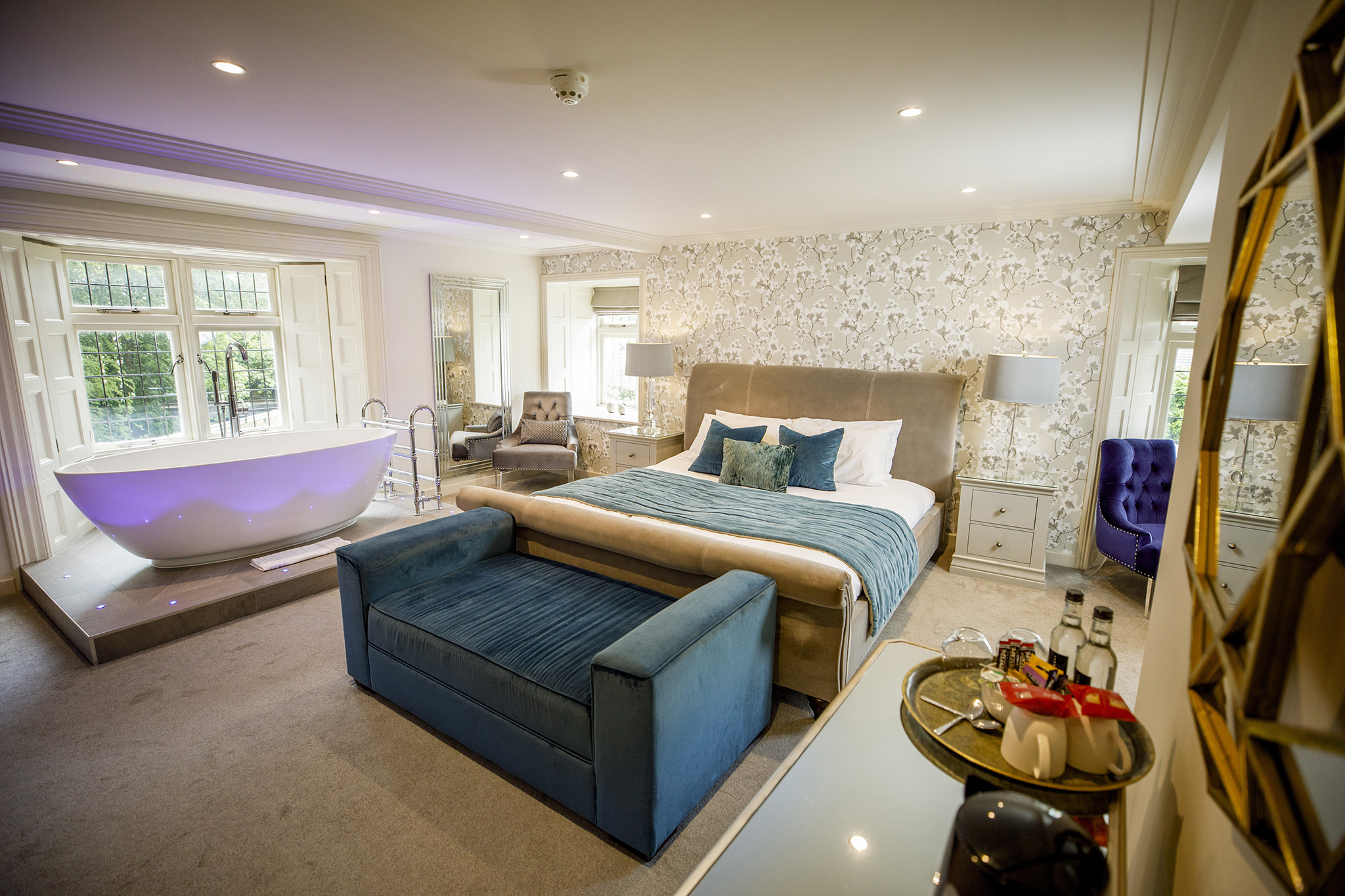 master hotel suite with large blue bed and ottoman with luxury decor and a large freestanding bath