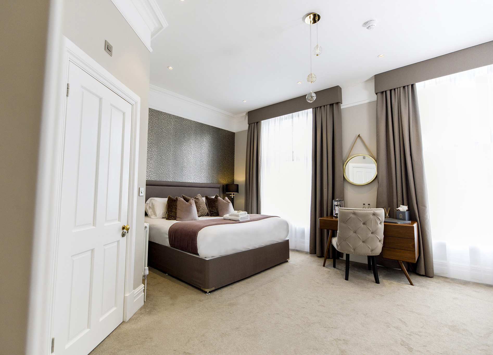 luxury hotel room with purple decor and large windows