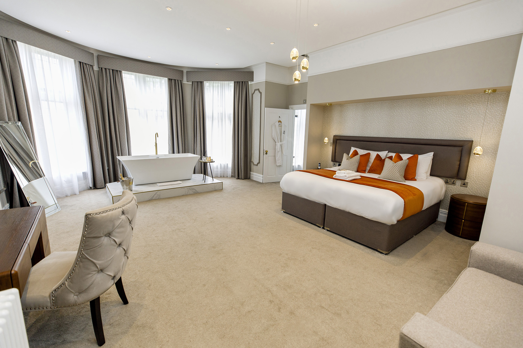 Deluxe hotel room suite with large orange bed and luxury bathtub